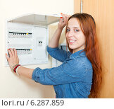 Купить «Long-haired smiling woman turning off the light-switch at power control panel», фото № 6287859, снято 20 июня 2013 г. (c) Яков Филимонов / Фотобанк Лори