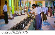 Купить «Мужчина наполняет масляные лампы в храме, Янгон, Мьянма», видеоролик № 6289775, снято 21 апреля 2014 г. (c) pzAxe / Фотобанк Лори