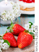 Ripe strawberries on wooden table. Beautiful scented candle decorated with fresh flowers in the background. Стоковое фото, агентство BE&W Photo / Фотобанк Лори