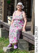 Купить «Пожилая женщина в летнем сарафане сидит около своего дома в деревне», фото № 6299307, снято 31 июля 2014 г. (c) Кекяляйнен Андрей / Фотобанк Лори
