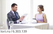 Couple with menus on tablet pc at restaurant. Стоковое видео, видеограф Syda Productions / Фотобанк Лори