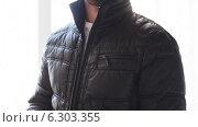 Close up of man unzipping his black jacket at home. Стоковое видео, видеограф Syda Productions / Фотобанк Лори