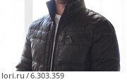 Close up of man zipping his black jacket at home. Стоковое видео, видеограф Syda Productions / Фотобанк Лори