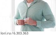 Купить «Close up of man buttoning his shirt at home», видеоролик № 6303363, снято 7 мая 2014 г. (c) Syda Productions / Фотобанк Лори