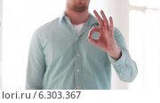 Купить «Man in shirt showing ok-sign», видеоролик № 6303367, снято 7 мая 2014 г. (c) Syda Productions / Фотобанк Лори