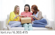 Купить «Smiling teenage girls opening cardboard box», видеоролик № 6303415, снято 8 мая 2014 г. (c) Syda Productions / Фотобанк Лори