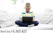 Купить «Smiling boy with tablet pc computer at home», видеоролик № 6303427, снято 12 июня 2014 г. (c) Syda Productions / Фотобанк Лори