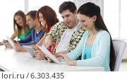 Купить «Smiling students with tablet pc at school», видеоролик № 6303435, снято 8 мая 2014 г. (c) Syda Productions / Фотобанк Лори