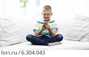 Купить «Smiling boy with smartphone at home», видеоролик № 6304043, снято 12 июня 2014 г. (c) Syda Productions / Фотобанк Лори