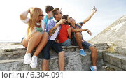 Купить «Group of smiling teenagers making selfie outdoors», видеоролик № 6304091, снято 12 августа 2014 г. (c) Syda Productions / Фотобанк Лори
