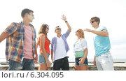 Купить «Group of smiling teenagers hanging out outdoors», видеоролик № 6304095, снято 12 августа 2014 г. (c) Syda Productions / Фотобанк Лори
