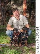 Улыбающийся мужчина в светлой рубашке держит двух собак-ягдтерьеров. Стоковое фото, фотограф Мороз Елена / Фотобанк Лори