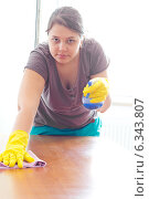 Купить «Молодая женщина в резиновых перчатках моет тряпкой деревянный стол», фото № 6343807, снято 7 июля 2014 г. (c) Ольга Марк / Фотобанк Лори