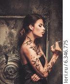 Купить «Smoking tattooed beautiful woman in old spooky interior», фото № 6346775, снято 19 июля 2014 г. (c) Andrejs Pidjass / Фотобанк Лори