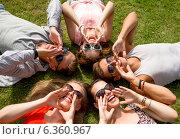 Купить «group of smiling friends lying on grass outdoors», фото № 6360967, снято 20 июля 2014 г. (c) Syda Productions / Фотобанк Лори