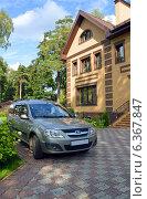 Автомобиль Лада Ларгус около загородного дома-коттеджа (2014 год). Редакционное фото, фотограф Александр Замараев / Фотобанк Лори