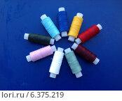 Купить «Набор цветных ниток для шитья на синем фоне», фото № 6375219, снято 11 мая 2014 г. (c) Светлана Голубкова / Фотобанк Лори
