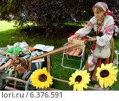 Купить «Ткачиха в народном костюме работает с помощью бердо (фокус на руках)», фото № 6376591, снято 15 августа 2014 г. (c) Ирина Борсученко / Фотобанк Лори