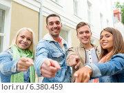Купить «group of smiling friends in city pointing finger», фото № 6380459, снято 14 июня 2014 г. (c) Syda Productions / Фотобанк Лори