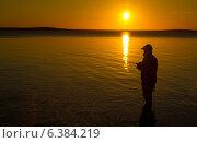 Рыбак со спиннингом на берегу озера на закате. Стоковое фото, фотограф Алексей Воронцов / Фотобанк Лори