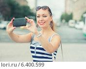Красивая молодая женщина фотографирует себя на телефон в городе. Стоковое фото, фотограф Darkbird77 / Фотобанк Лори