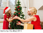 Купить «smiling family decorating christmas tree», фото № 6402911, снято 26 октября 2013 г. (c) Syda Productions / Фотобанк Лори