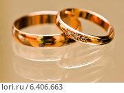 Купить «Два золотых обручальных кольца лежат на стекле», эксклюзивное фото № 6406663, снято 1 августа 2014 г. (c) Игорь Низов / Фотобанк Лори