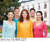 Купить «group of smiling teenagers over campus background», фото № 6409227, снято 22 июня 2014 г. (c) Syda Productions / Фотобанк Лори