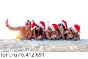 Купить «group of friends in santa hats with smartphone», фото № 6412691, снято 3 августа 2014 г. (c) Syda Productions / Фотобанк Лори
