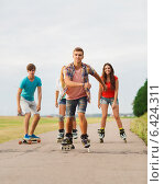 Купить «group of smiling teenagers with roller-skates», фото № 6424311, снято 10 августа 2014 г. (c) Syda Productions / Фотобанк Лори