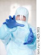 Эпидемиолог в защитном костюме протягивает руки к зрителю, фото № 6425903, снято 20 сентября 2014 г. (c) Эдуард Паравян / Фотобанк Лори