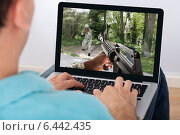 Купить «Man Playing Action Game On Laptop», фото № 6442435, снято 22 марта 2014 г. (c) Андрей Попов / Фотобанк Лори
