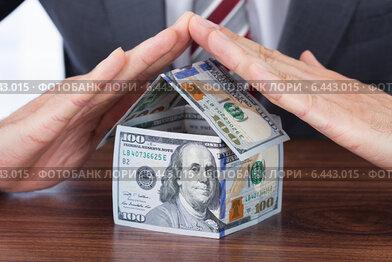 Купить «Businessman Sheltering House Made With Bank Notes», фото № 6443015, снято 7 мая 2014 г. (c) Андрей Попов / Фотобанк Лори