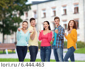 Купить «group of smiling teenagers over campus background», фото № 6444463, снято 22 июня 2014 г. (c) Syda Productions / Фотобанк Лори
