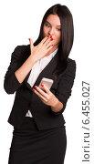 Купить «Длинноволосая брюнетка в деловом костюме удивленно смотрит на телефон», фото № 6455027, снято 4 сентября 2014 г. (c) Кирилл Черезов / Фотобанк Лори