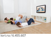 Family Doing Situps While Watching TV. Стоковое фото, фотограф Андрей Попов / Фотобанк Лори