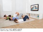 Купить «Family Doing Situps While Watching TV», фото № 6455607, снято 14 июня 2014 г. (c) Андрей Попов / Фотобанк Лори