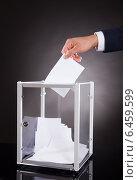 Купить «Businessman Inserting Ballot In Box On Desk», фото № 6459599, снято 10 апреля 2014 г. (c) Андрей Попов / Фотобанк Лори