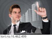 Купить «Businessman Touching Transparent Screen With Growing Bar Graph», фото № 6462499, снято 28 июня 2014 г. (c) Андрей Попов / Фотобанк Лори