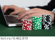 Купить «Businessman Using Laptop By Stacked Casino Chips», фото № 6462819, снято 28 июня 2014 г. (c) Андрей Попов / Фотобанк Лори