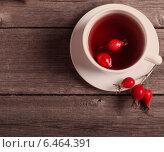 Купить «cup of tea with hip roses, on wooden table», фото № 6464391, снято 7 сентября 2014 г. (c) Майя Крученкова / Фотобанк Лори