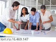 Купить «Team of architects going over blueprints», фото № 6469147, снято 18 июня 2019 г. (c) Wavebreak Media / Фотобанк Лори