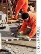 Рабочий укладывает тротуарную плитку (2014 год). Редакционное фото, фотограф Яна Королёва / Фотобанк Лори