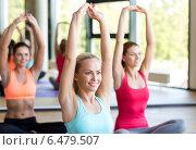 Купить «group of smiling women stretching in gym», фото № 6479507, снято 7 июня 2014 г. (c) Syda Productions / Фотобанк Лори