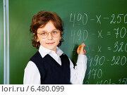 Купить «Школьник в очках пишет мелом на доске в классе», фото № 6480099, снято 16 августа 2014 г. (c) Сергей Новиков / Фотобанк Лори