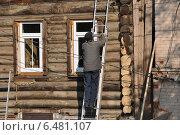 Купить «Рабочий на лестнице ремонтирует старый бревенчатый жилой дом в Павловском Посаде», эксклюзивное фото № 6481107, снято 18 сентября 2014 г. (c) lana1501 / Фотобанк Лори