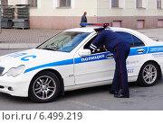 Инспектор ДПС разговаривает с полицейским, сидящим за рулём машины ДПС (2014 год). Редакционное фото, фотограф Маркин Роман / Фотобанк Лори