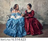 Купить «Две красивые девушки в старинных платьях с книгой», фото № 6514623, снято 10 апреля 2014 г. (c) Darkbird77 / Фотобанк Лори