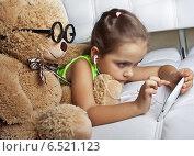 Купить «Девочка в наушниках с игрушечным медведем смотрят в мобильный телефон», фото № 6521123, снято 9 октября 2014 г. (c) Элина Гаревская / Фотобанк Лори