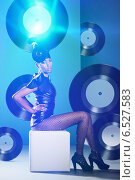 Disco woman on the chair with vinyl records and neon light. Стоковое фото, фотограф Александр Буц / Фотобанк Лори